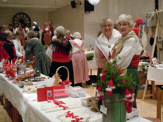 Full rulle i Forsslundssalen, nationaldräkter, folkdans på scen, bord fyllda med hantverk.