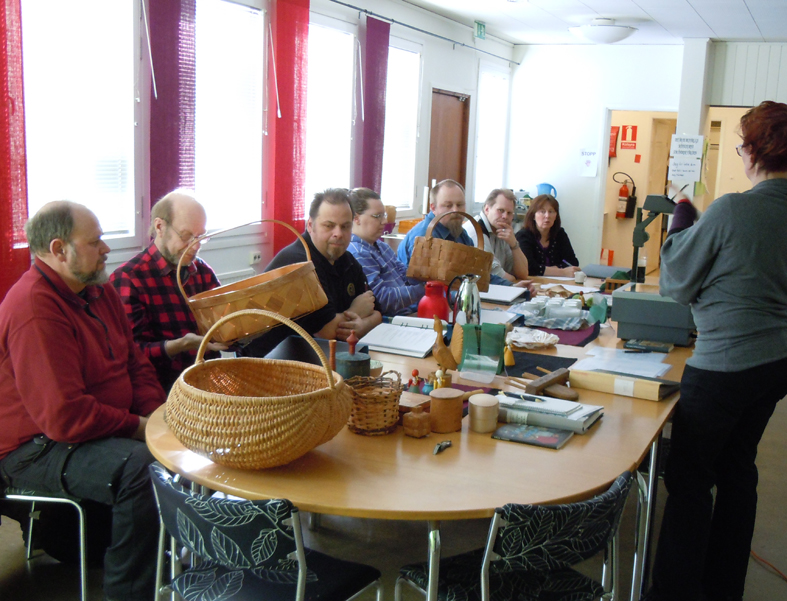 Undervisning på Kulturarvet, Maria Björkroth visar korgarbeten. Från vänster sitter Björn, Lars, Claes, Nina, Thomas, Per och sist Kia Wegelius som ansvarar för verksamheten.