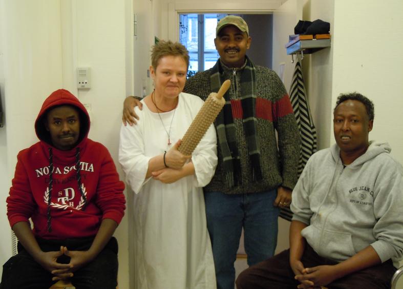 Somalier bakar bröd med Eva Långberg. Fr vä Ahmed Mohammed Abdillaji, Nurudin Mohammud och Abdi Quuri längst t hö.  Eva Långberg viftar med kaveln.