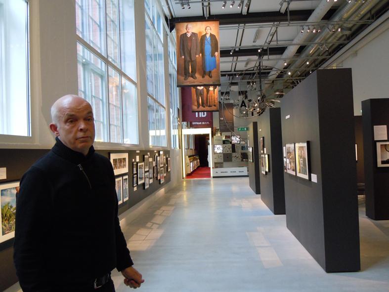 Carl-Magnus Gagge berättar om utställningen. Rummet är en jättehall med sidoutrymmen. Ett underbart ljus strilar in.