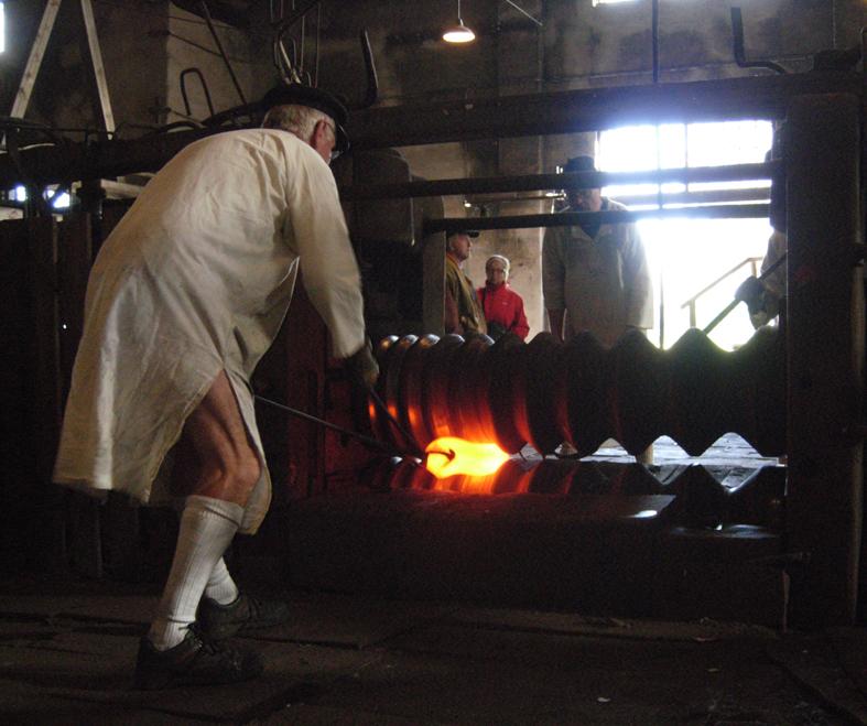 """En snygg smed med fina benmuskler valsar ut stångjärn i Karmansbo lancashiresmedja i Ekomuseum. Detta kan man beskåda på """"Järnets dag"""" varje år den första lördagen i juli. Som just passerat för er som vill dit, tyvärr. Men smedjan är öppen nu i juli för besök och smeder som visar runt finns det. Foto ChL."""