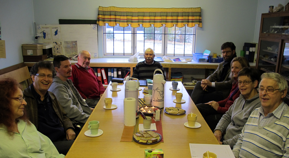"""I """"Såga"""", ett hus som står kvar efter sågen som låg härnere vid sjön Liens strand, där samlades vi och diskuterade rastplatsen över en kopp kaffe. Från vänster sitter: Marlène Carlsson, Staffan Bergman och Marco Helmisaaro, samtliga från kommunen. Därefter Johan Torvaldsson och Nils-Eric Wikström vid bordsänden, båda engagerade bybor, till höger om honom Jan Jävert och Anna Jansson, båda från kommunen, sen Barbro Bergkvist och Kalle Nordebring, även de två är engagerade bybor."""